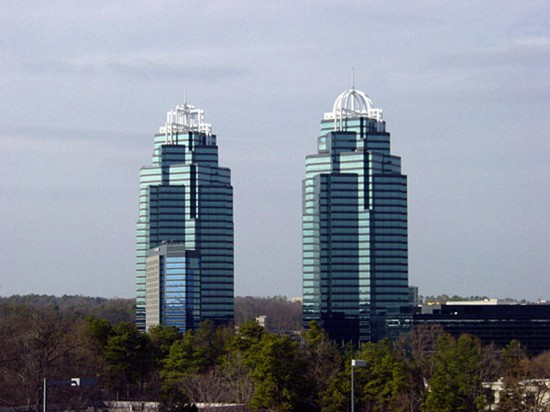 "These high-rise office towers are a familiar landmark along Atlanta's I-285 beltway, known as the Perimeter. The ""King and Queen"" buildings express a vision of automobile-scaled architecture, their reflective-glass walls rising from the greenery of a planned development. The problem of Atlanta's traffic congestion, and the role of commuter destinations such as these, is not immediately visible from this idyllic perspective."
