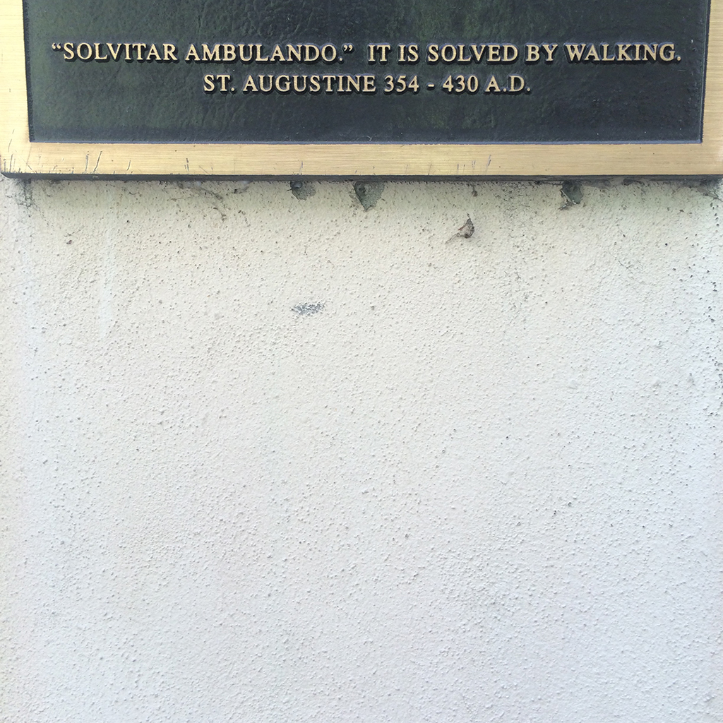 "Image of bronze plaque reading, """"Solvitar Ambulando.' It is solved by walking. St. Augustine 354-430 A.D."